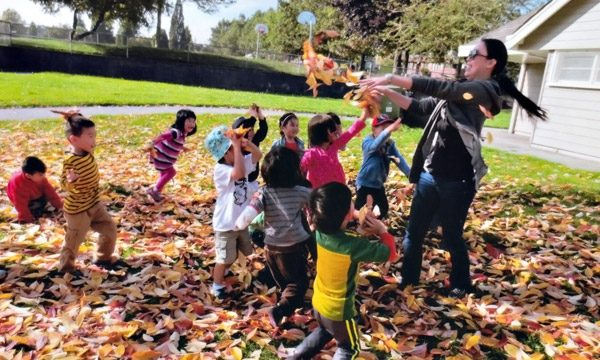 Brainbridge preschool students playing with autumn leaves.