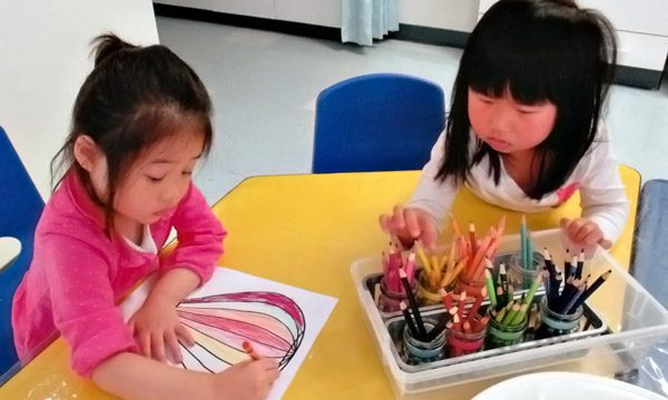 Two girls are colouring hot air balloons.