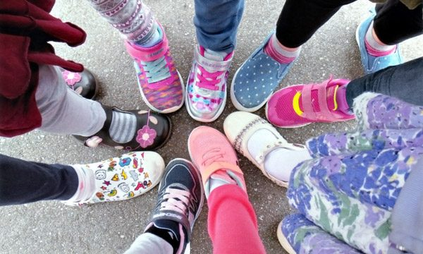 Students play outdoors, girls feet gather in the middle.